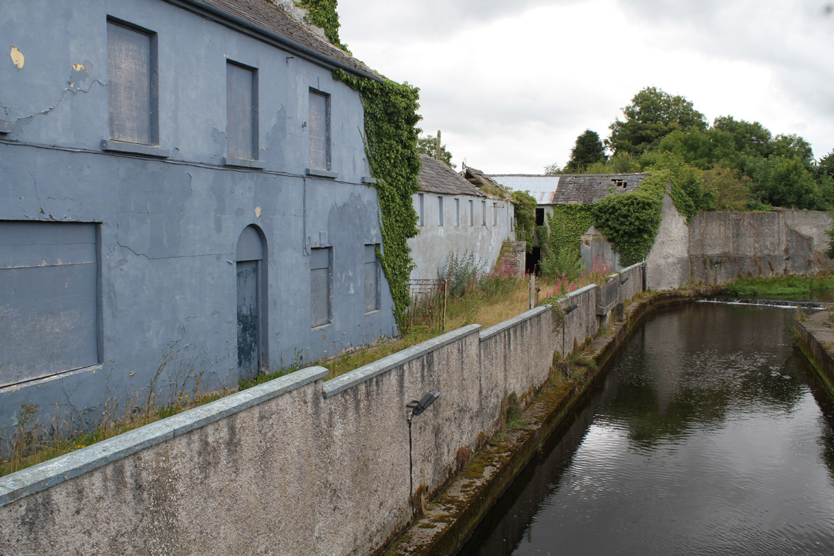 A photograph of the riverfront industrial buildings in Charlestown, Ireland, long shuttered and painted over; moss and ivy grow over the buildings and walls surrounding